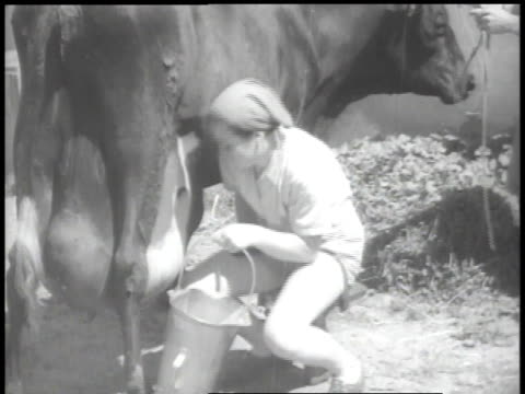1938 MONTAGE Two girls smiling at camera and woman milking a cow