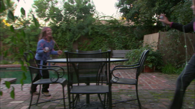 ws, two girls (10-11) squirting party strings in garden, los angeles, california, usa - squirting stock videos and b-roll footage