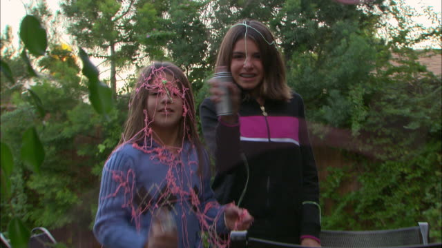 cu, zo, zi, two girls (10-11) squirting party strings in garden, los angeles, california, usa - squirting stock videos and b-roll footage