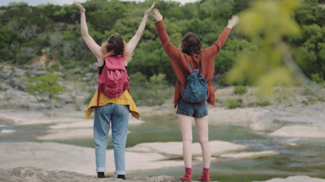Two girls stop and throw hands in the air and dance overlooking river while hiking in Pedernales Falls State Park.