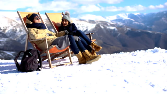 stockvideo's en b-roll-footage met twee meisjes zonnebaden in lounge stoelen op de winterdag - sunbathing