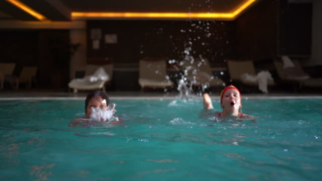 zwei mädchen schwimmen im pool - schwimmflügel stock-videos und b-roll-filmmaterial