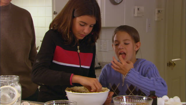 ms, two girls (10-11) tasting cookie dough in kitchen - 10 11 jahre stock-videos und b-roll-filmmaterial