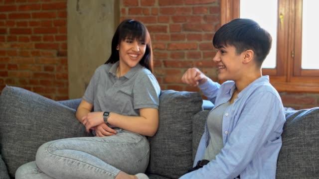 two girls, teenagers, using digital tablet on living room sofa - teenage girl watching tv stock videos & royalty-free footage