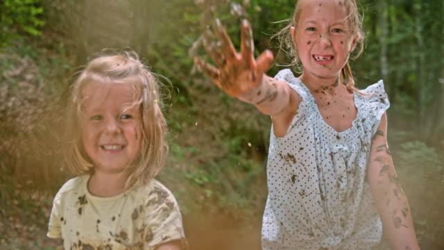 stockvideo's en b-roll-footage met slo mo twee meisjes modder gooien in de cameralens - haar naar achteren