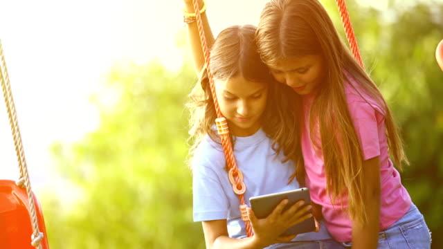 vídeos y material grabado en eventos de stock de dos chicas usando tableta digital. - imagen virada