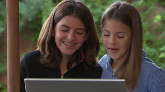 vídeos de stock, filmes e b-roll de cu, two girls (10-11) using laptop and laughing outdoors, los angeles, california, usa - brace