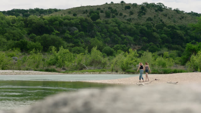 vidéos et rushes de two girls walk down sandy beach and sit down by riverside in pedernales falls state park. - personnes féminines