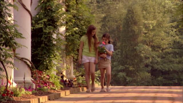 stockvideo's en b-roll-footage met two girls walk on a brick pathway sharing a potted flower. - tuinpad
