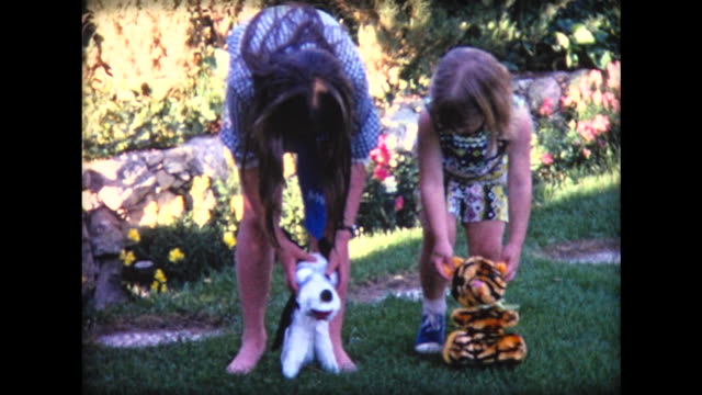 1971 two girls walk stuffed animals across lawn