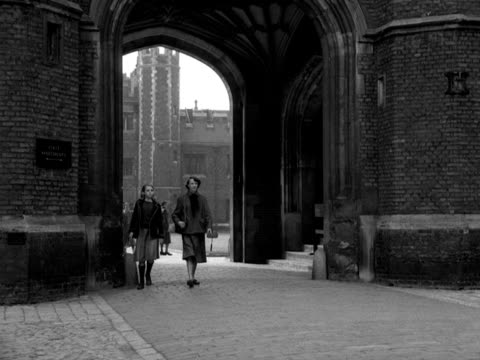 two girls walk through ann boleyn's gate at hampton court palace. 1950's. - ruler stock videos & royalty-free footage