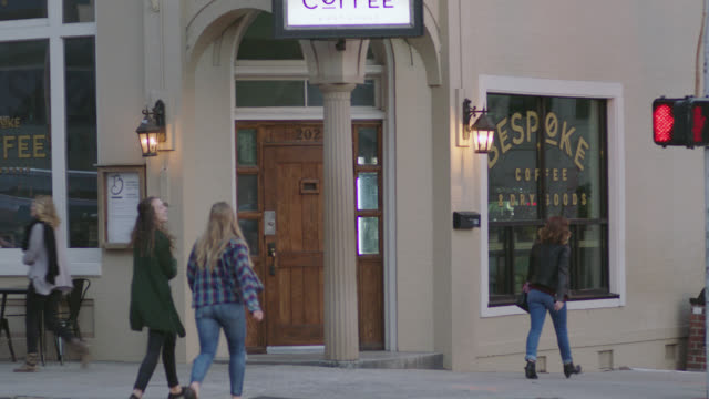 two girls walk up to local coffee shop on downtown street corner. - ecke eines objekts stock-videos und b-roll-filmmaterial
