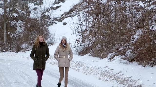 Twee meisjes lopend en pratend, winters tafereel