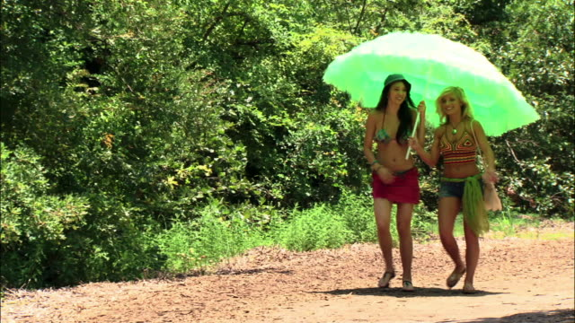 ws two girls walking down dirt road under sunshade/ texas - belly button piercing stock videos & royalty-free footage