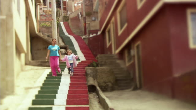 LA WS Two girls walking down long length of painted steps / Bogota, Colombia