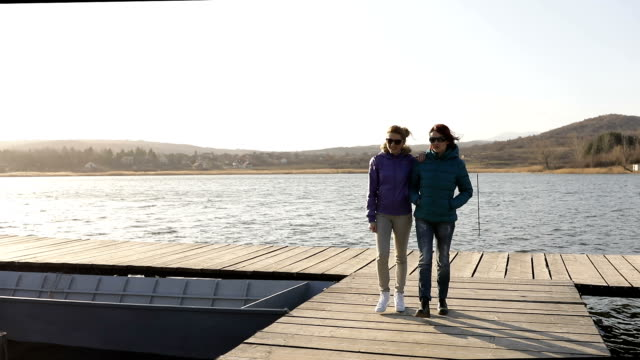 two girls walking on a lake dock - lesbica video stock e b–roll