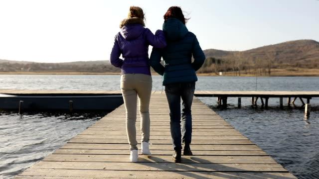 vidéos et rushes de deux filles marchant sur un lac quai - allée couverte de planches