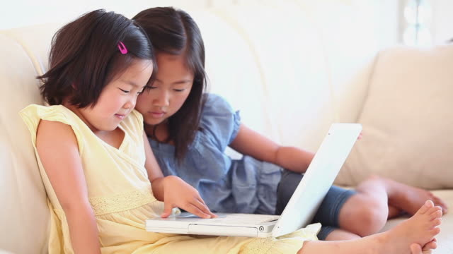 two girls watching something on a laptop - hair accessory stock videos & royalty-free footage