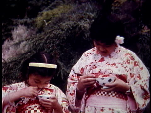 montage ms two girls wearing kimonos and eating bowls of rice / cu tu girl eating rice with chopsticks / unknown location - kimono stock videos & royalty-free footage