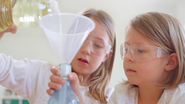 科学実験をしている保護眼鏡をかけた2人の女の子 - 解決策点の映像素材/bロール