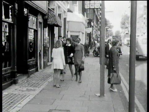 two girls wearing sixties style mini dresses walk down street towards camera and into mod shop london - street style点の映像素材/bロール