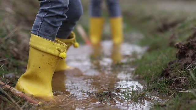 黄色いブーツを履いた二人の女の子が泥水の中で遊んでいる - ヨゴレ点の映像素材/bロール