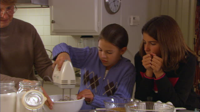 CU, PAN, Two girls (10-11) with grandmother mixing cookie dough in kitchen