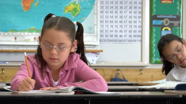 cu, pan, two girls (8-9) writing in classroom - video ritratto video stock e b–roll