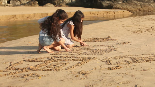 vídeos de stock, filmes e b-roll de two girls writing on sand on the coast - ajoelhando se