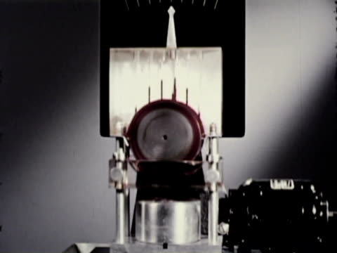stockvideo's en b-roll-footage met 1951 montage two glass colanders form columns of red and blue oil for side-by-side comparison of viscosity, scientist in background, model being rotated to show motor gears / usa / audio - motor oil