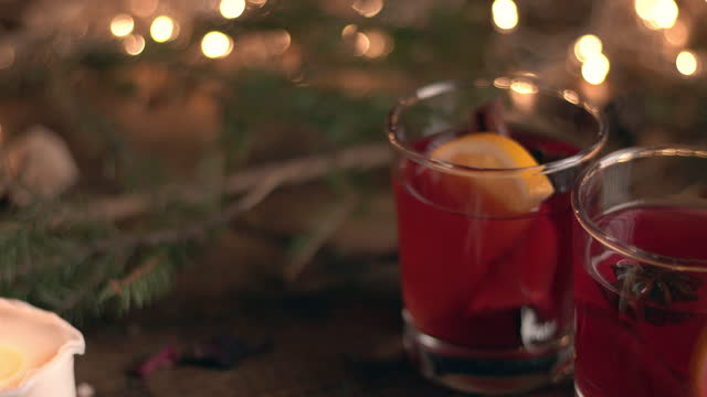 vídeos de stock e filmes b-roll de two glasses of mulled wine on a background of fir branches and burning candles - bebida quente