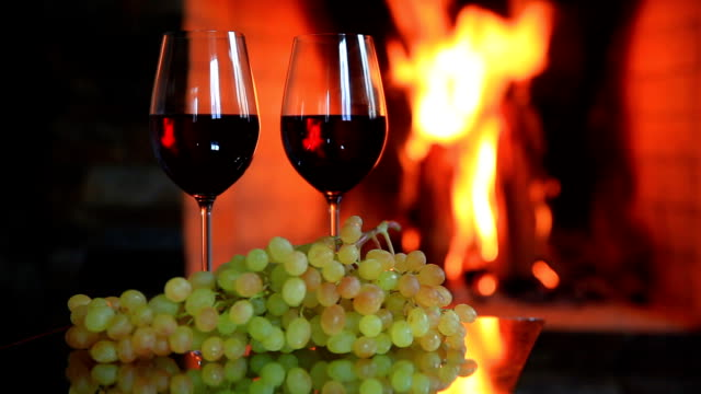 Two glasses of red wine with grapes near the fireplace in the evening