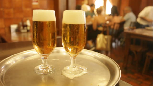 two glasses of refreshing beer,  shot on a restaurant inside public market, porto alegre, rio grande do sul - porto alegre stock-videos und b-roll-filmmaterial