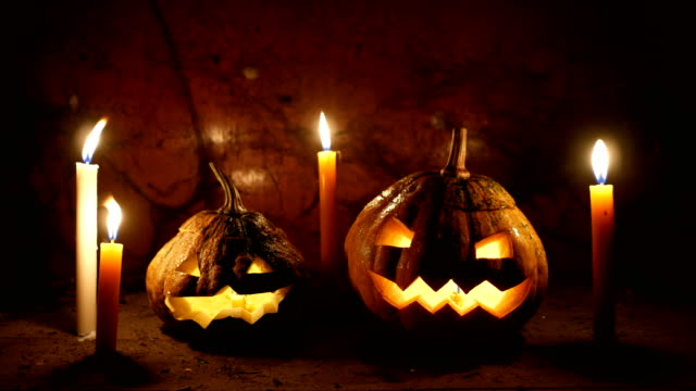 vídeos de stock e filmes b-roll de two glowing pumpkins jack-o-lantern with candles on old wood floor in dark, halloween theme - lagenaria