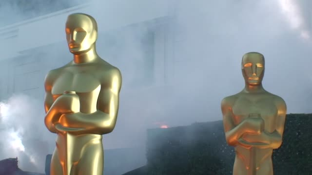 vídeos de stock e filmes b-roll de two golden oscar statues in smoke searchlights on march 07 2010 in los angeles california - estátua