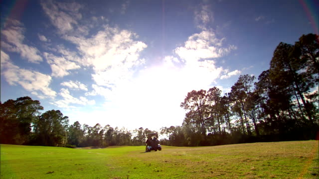 Two golf carts w/ unidentifiable male golfers moving away from camera down green grass of course toward trees in BG blue sky Fairway golfing putting...
