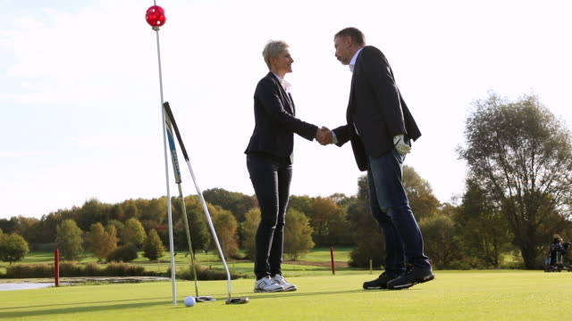 Two golf players shaking hands