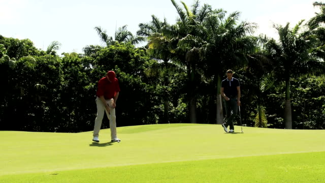 Two golfers on a putting green