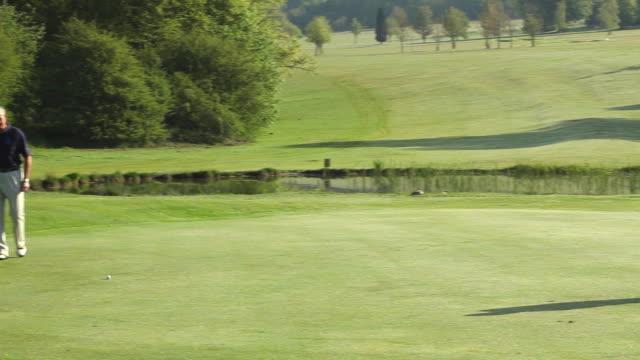 vídeos y material grabado en eventos de stock de ws pan two golfers on green putting out and shaking hands / canterbury, kent, uk - putt