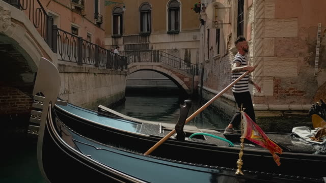 stockvideo's en b-roll-footage met two gondolas passing each other in a narrow canal filmed from a side on view, venice, italy - italian culture