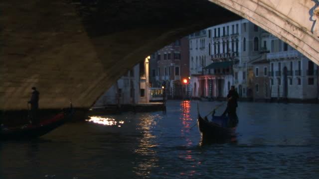 vídeos y material grabado en eventos de stock de cu, zo, two gondolas passing under realto bridge at dusk / venice, italy - puente de rialto