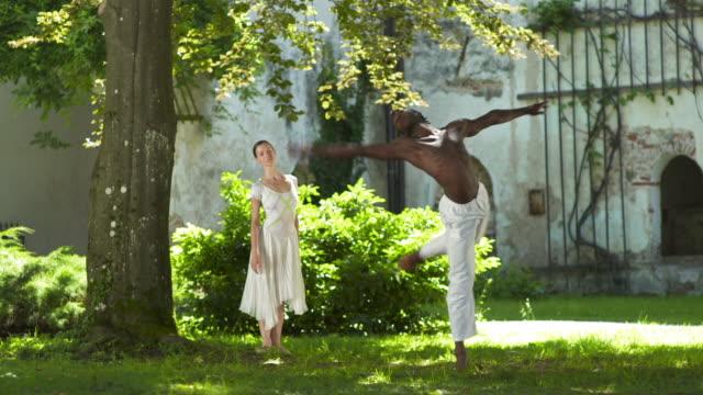 vídeos y material grabado en eventos de stock de dolly hd: dos bailarines de ballet elegantes en el parque - de puntas
