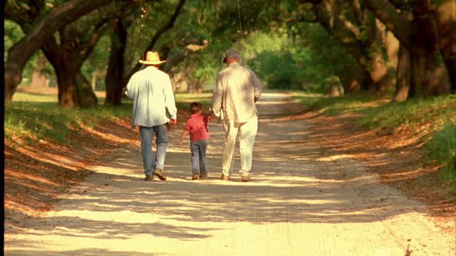vídeos de stock e filmes b-roll de two grandfathers and their grandson walk under trees with fishing poles. - wilmington carolina do norte