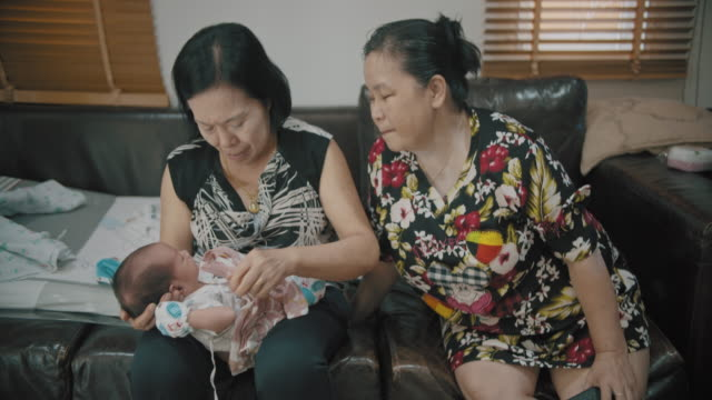 two grandmothers were holding grandson. - 0 1 months stock videos & royalty-free footage