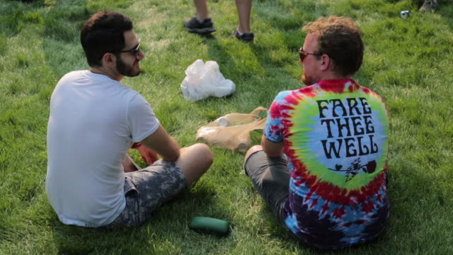 two grateful dead fans, one wearing a tie-dyed shirt, sits on a lawn south of soldier field before the show on the 4th of july. the grateful dead... - fare video stock e b–roll