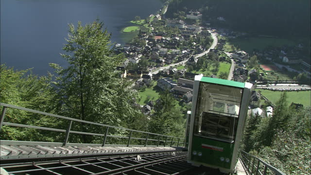 vídeos de stock e filmes b-roll de two green mountain railway cars pass each other on mountainside above town overlooking hallstattersee, hallstatt - cultura austríaca