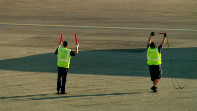 vídeos de stock e filmes b-roll de ws, two ground controllers directing aircraft traffic, los angeles, california, usa - alfalto