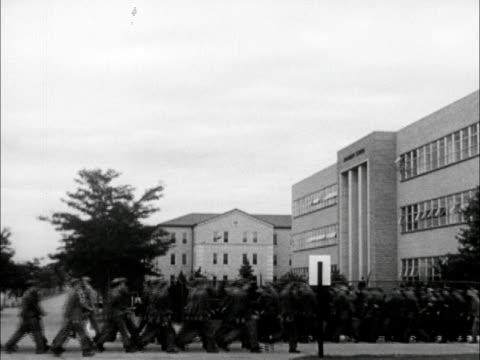 two groups of us air force soldiers passing on sidewalk one group moving away from building other toward xws soldiers walking into armament school... - us air force stock videos & royalty-free footage