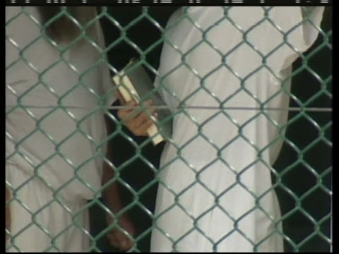 two guantanamo bay detainees speak by a fence while one holds a book - crime or recreational drug or prison or legal trial stock-videos und b-roll-filmmaterial