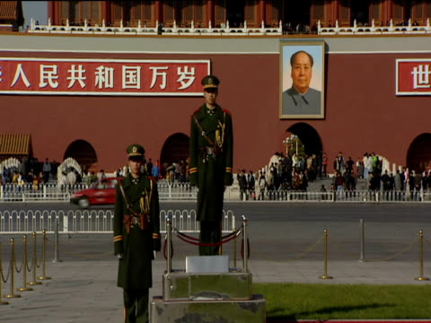 two guards dressed in green uniforms stand in front of gateway to forbidden city mao picture hanging on wall. traffic and cyclist pass in background beijing - maoism stock videos & royalty-free footage